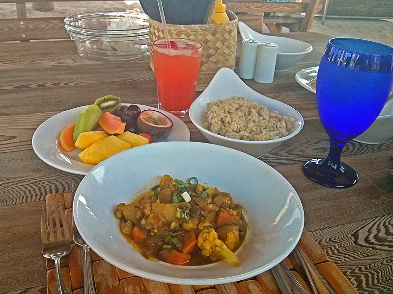 Savory vegetable curry with fresh fruit, brown rice, and a Bahama Mama