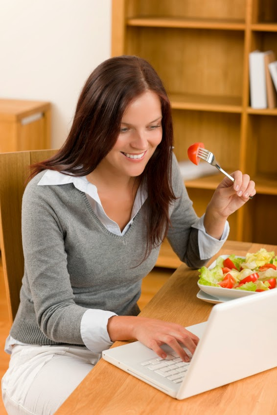 Working lunch at home attractive woman with laptop eat salad