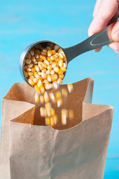 Pouring popcorn in a brown bag to microwave for popcorn